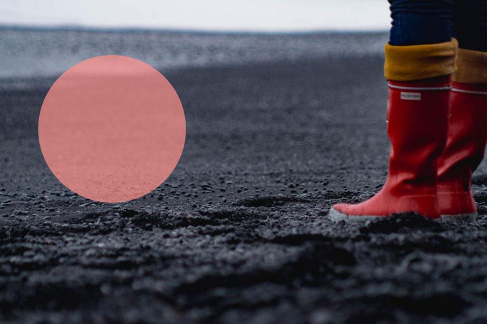 Südisland: Roter Gummistiefel am schwarzen Strand